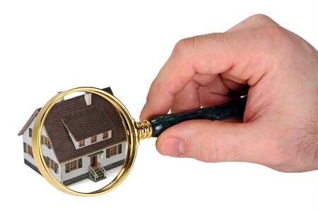 housing search: Immagine del concetto di un controllo domestico. Una mano maschile detiene una lente di ingrandimento su una casa in miniatura. Sfondo bianco