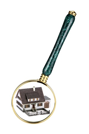 A magnifying glass examining a miniature model home. Concept image of a home inspection. Isolated on white. photo