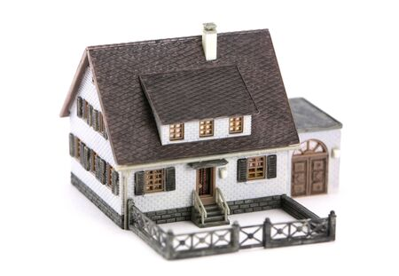 A miniature model home. Home is only 2 inches tall. It has white brick, shutters on the windows and a brown shingled roof. There is a picket fence in front. Isolated on white background.