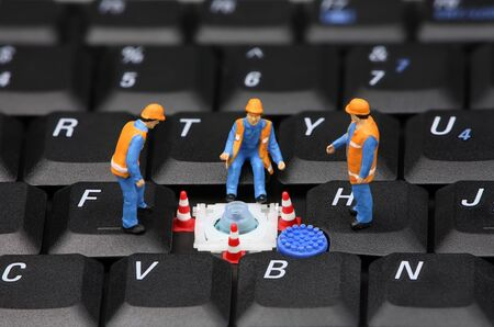 Group of miniature computer technicians repairing a missing key on a laptop keyboard. Computer repair concept. photo