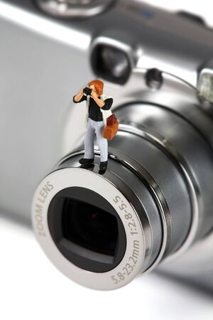 A miniature photographer holding a camera is standing on a full-sized camera.