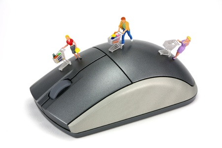 Concept image of shoppers on a computer mouse to represent online internet shopping. The shoppers have shopping carts. White background.