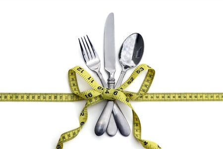 spoon and fork: A set of silverware tied with a measuring tape in a bow. White background. Good for healthy eating or dieting concept.