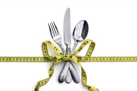 cuchara: Un conjunto de plater�a atado con una cinta de medici�n en un arco. Fondo blanco. Bueno para comer o concepto de dieta saludable. Foto de archivo
