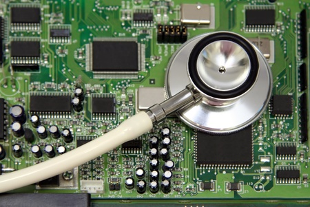 uses a computer: A stethoscope on a computer circuit board. Possible concept uses: computer health,  technology in healthcare, diagnosingtroubleshooting PC problems, medical technology.