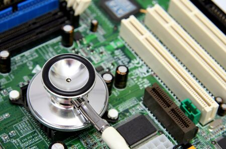 A stethoscope on a computer motherboard. Possible concept uses: computer health, technology in healthcare, diagnosingtroubleshooting PC problems, medical technology. Stock Photo