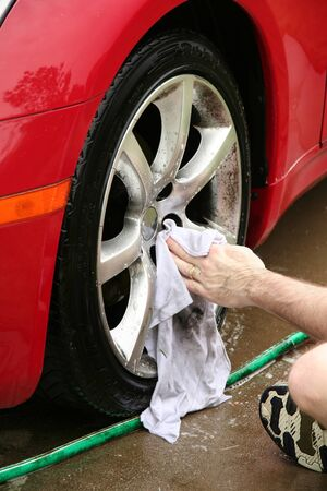 water wheel: A man washing a wheel of a car.  There is slight motion blur on the hand as it washes. Stock Photo