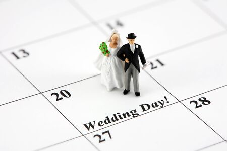 miniature people: Concept image of a bride and groom standing on a calendar date that says Wedding Day.