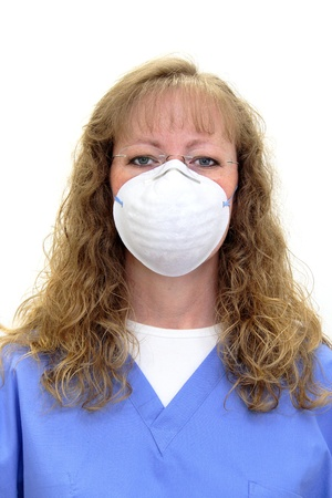 Nurse or dental hygienist in scrubs wearing a protective mask and eye glasses. Isolated on white. photo