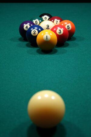 snooker balls: 9-Ball rack of billiard balls on a green felt pool table.