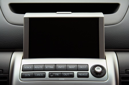 A close-up view of a GPS vehicle navigation system inside a car.  Screen is blank so you can add your own.