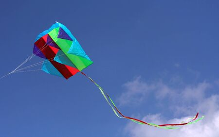 kiting: Colorful parafoil kite in flight with a blue sky background Stock Photo
