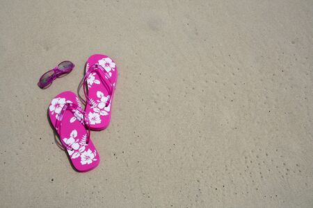 Pink flip-flops and sun glasses on the sand at the beach photo