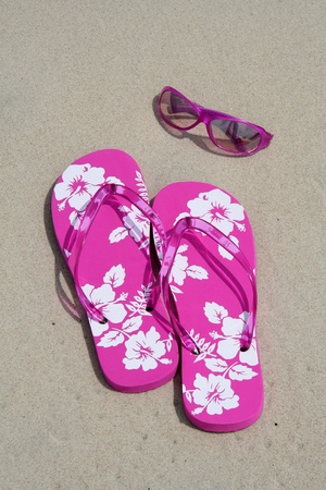 break: Pink flip-flops and sun glasses on the sand at the beach