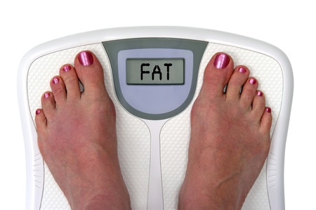 gain: Feet on a bathroom scale with the word fat on the screen.