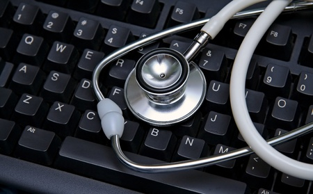 A white stethoscope on a black computer keyboard. Stock Photo
