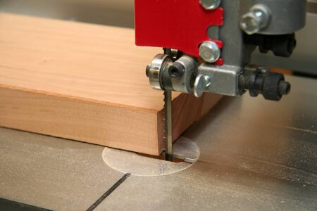 machines: Bandsaw blade up close as its about to cut a piece of wood. Very shallow depth of field. Stock Photo