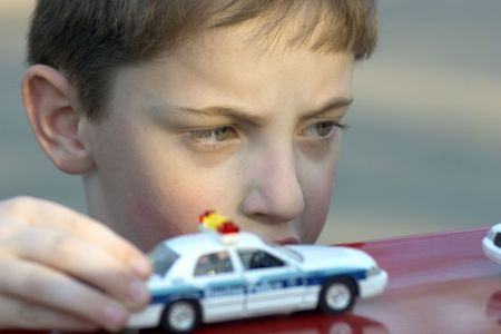 imitate: Boy playing with toy police cars