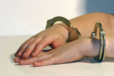 Childs hands in handcuffs resting on table photo