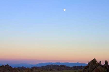 A moonrise at sunset over some high desert hills Stock fotó