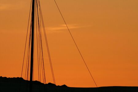 An abstract look at a sailboats mast silhouetted against a sunset Stock fotó