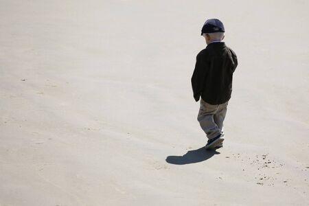 ビーチで単独で歩いて小さな男の子