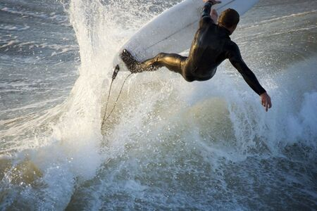 A surfer hits the top of a wave and appears to fly