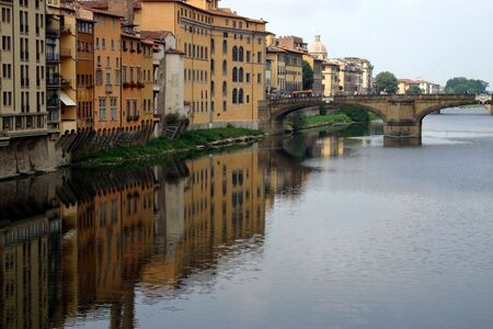 A bridge over a scenic Italian river bordered by colorful buildings and their reflections Stock fotó