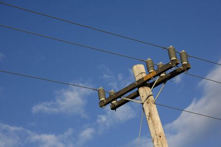 A high voltage power pole against a blue sky