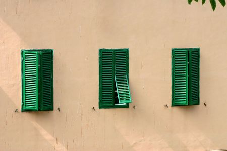 Three bright green shutters on a flat, plain building