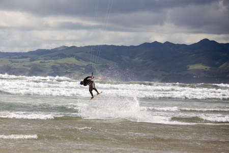 A kiteboarder takes to the air on a rainy day