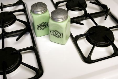 Antique salt and pepper shakers on a stove Stock fotó