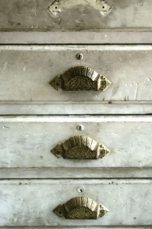 Close-up look at an old set of drawers with brass handles