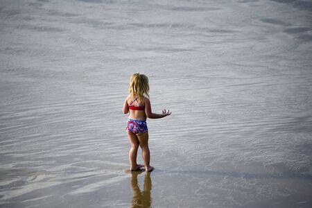 不思議そうに海岸に立っている少女 写真素材