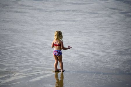 A little girl stands on the shore in wonder Stock fotó