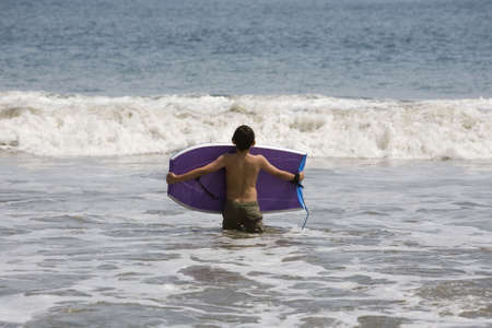 A child new to boogie boarding awaits the next wave