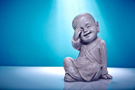 Close Up image of a laughing stone buddah isolated on a blue background