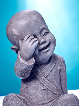 buddah: Close Up image of a laughing stone buddah isolated on a blue background