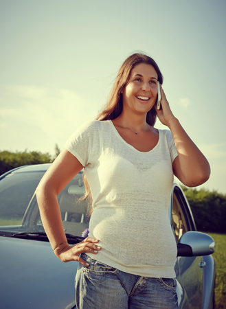Car Woman is talking on her phone next to her car on a bright sunny summer day. photo