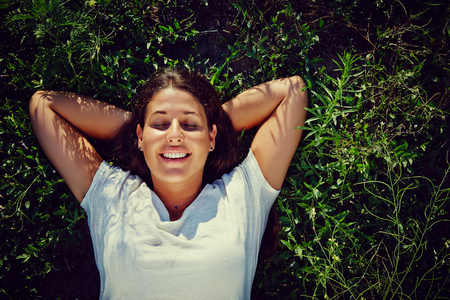 Beautiful girl lying down in grass, relaxing in the sun. Copy space around her.  Click for more: photo