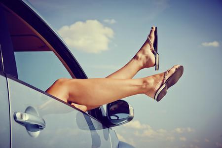 femme sexe: Road Trip concept. Femme bloque Ses jambes par la fenêtre dans la voiture. Banque d'images