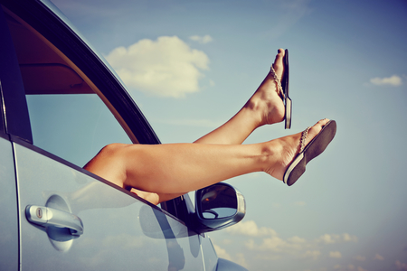 woman sex: Road trip concept. Woman Hangs Her legs out of window in car.
