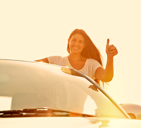 Driver Woman showing thumbs up, is Happy With Her new Car. photo