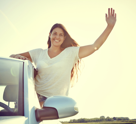 Young driver Woman Waving out of her new car, rental car. photo