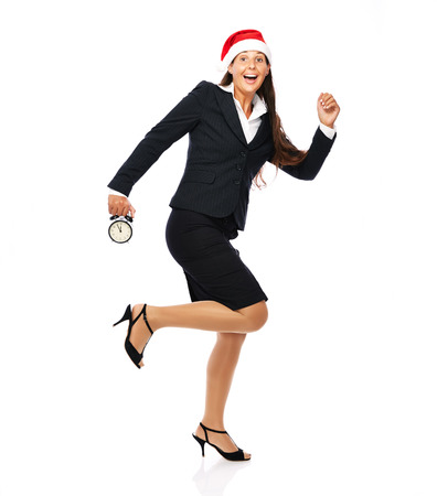Business woman with santa hat is running holding a clock showing 5 to 12.   Isolated on a white background.  photo