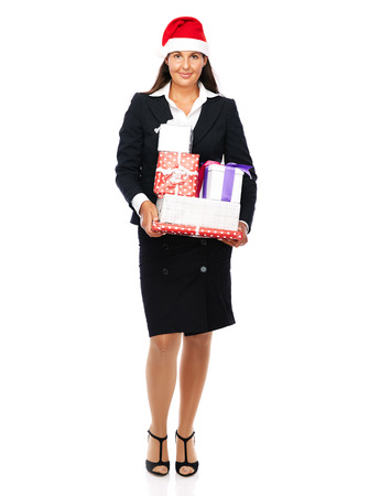 Business woman wearing a santa claus hat holding parcels in her hands and is smiling.   Isolated on a white background.  photo