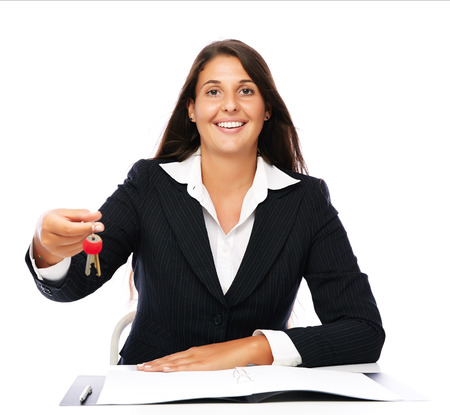 Business woman sitting at desk with documents giving keys to the new house odner.Isolated on a white background. photo