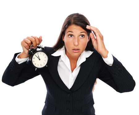 getting late: Business woman holding a clock that shows 5 to 12. Concept for stress or getting late. Isolated on a white background.