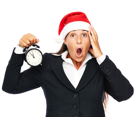 Business woman wearing santa claus hat holding a clock showing 5 to 12.   Isolated on a white background.  photo