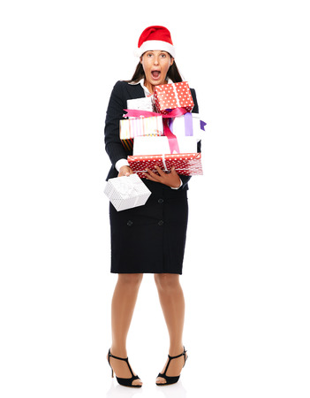 Business woman with santa claus hat is holding parcels and has christmas stress.   Isolated on a white background.  photo